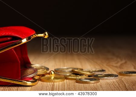 female red wallet with coins on wooden table, on black background