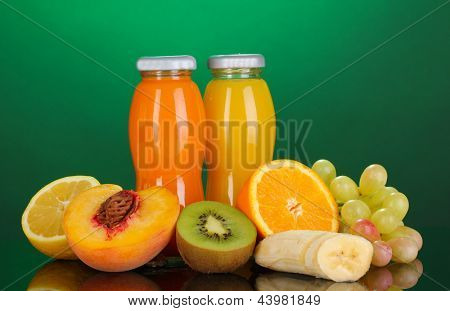 Delicious multifruit juice in a bottle and fruit next to it on green background