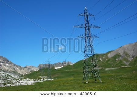 electricity pylons crossing the Bernese Alps. These cables transport electricity from the major hydro-electric generating areas in the high alps to the industrial towns in the north of switzerland. To cut down on losses the most direct route is taken this poster