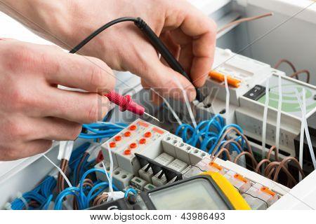 Manos de un electricista con sonda multímetro en un gabinete de Aparamenta eléctrica