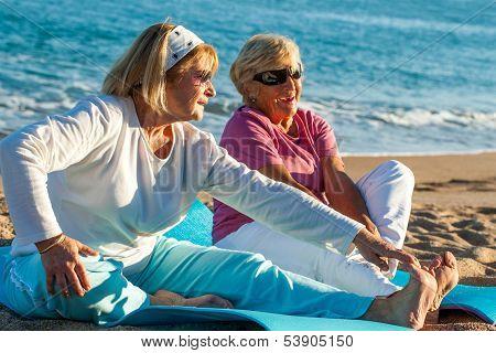 Elderly Women Doing Stretching Exercises On Beach.