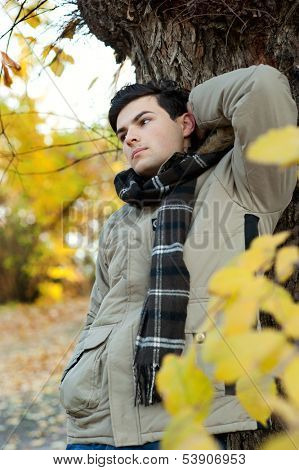 Young dreaming man standing in autumn park.