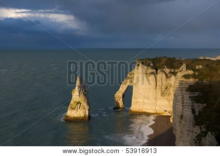 Etretat cliffs with stormy sky background in Normandy France in sunset poster