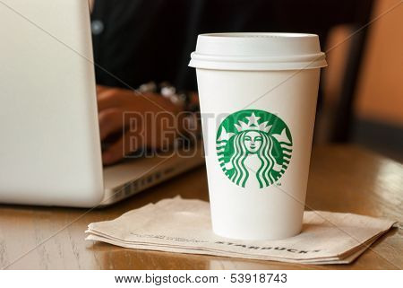 SCARSDALE, NY - SEPTEMBER 15, 2013: A tall Starbucks coffee in front of a woman working on a laptop computer.