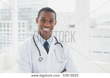 Portrait of a confident smiling male doctor standing in a medical office