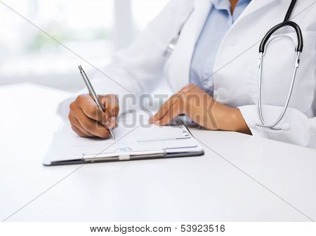 healthcare and medical concept - female doctor writing prescription