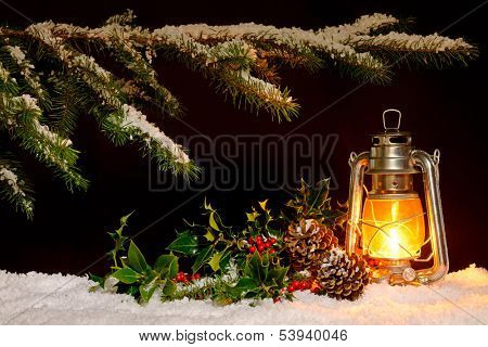 Christmas scene - an oil filled lantern burning bright with snow covered tree, holly and ivy lit up by the glow of the lamp.