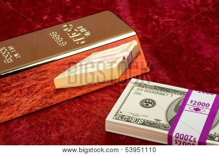 A gold bar with a pile of American cash on red crushed velvet for use as a precious metal investment inference.