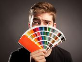 young man holding a pantone palette poster