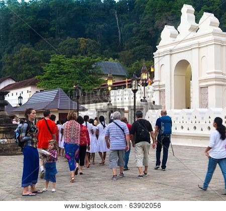 KANDY, SRI LANKA - FEBRUARY 26, 2014: Tourists in front of The Temple of the Tooth Relic, one of the most sacred Buddhist places of worship situated in UNESCO World Heritage Site.