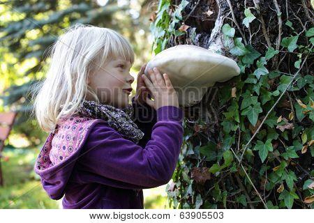Little caucasian girl examining large Tinder fungus on tree bark - early education