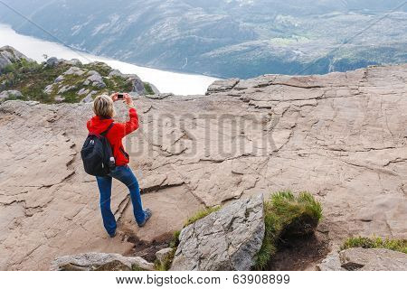 Woman hiker on Pulpit Rock / Preikestolen, Norway capturing photo of Lysefjorden view.  Pulpit rock is a massive cliff 604 metres above Lysefjorden, almost flat, and is a famous tourist attraction in Norway. poster