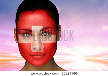 Composite image of beautiful brunette in swiss facepaint against beautiful blue and yellow sky