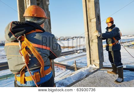 Team of builder worker in safety protective equipment at winter construction site