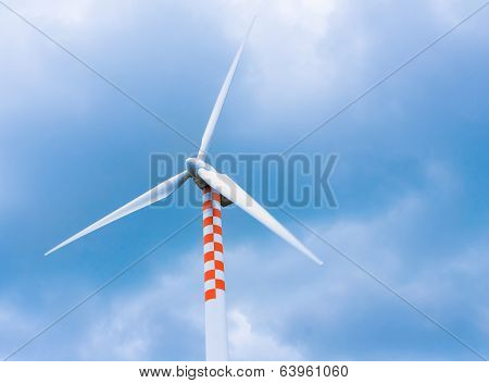 Wind Turbine In Movement Under Blue Sky And Clouds