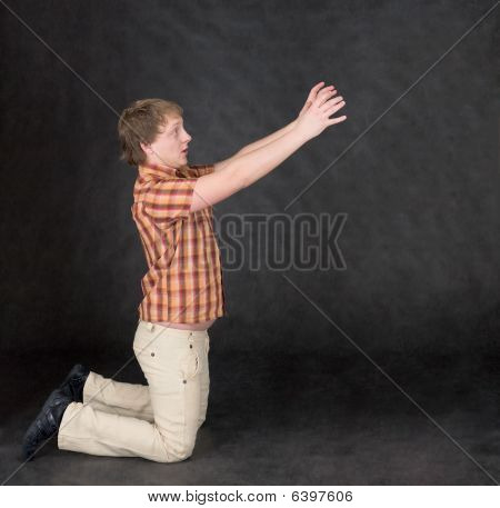 Amusing Young Man Is Kneeling And Stretch Hands To Something
