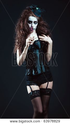 Young Woman In The Image Of Sad Gothic Freak Clown Smelling Withered Flower