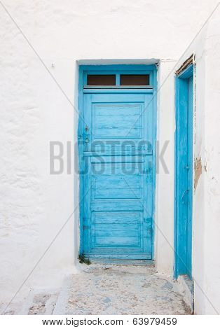Old Painted Blue Door On The Whitewashed Wall. Background. Typical For Greece...