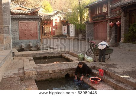 Chinese Naxi Woman Washing On Ancient Pool .