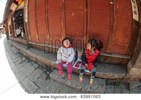 Little Girls Sitting And Happiness In Lijiang Dayan Old Town.