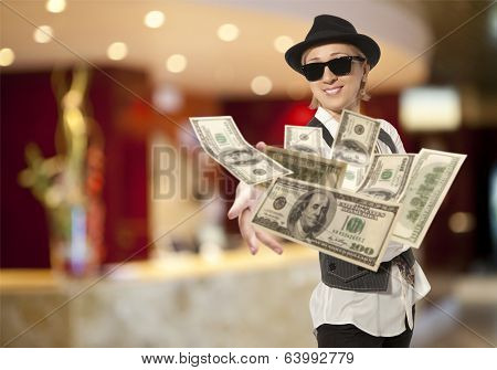 Handsome adult business woman in cap throwing dolla