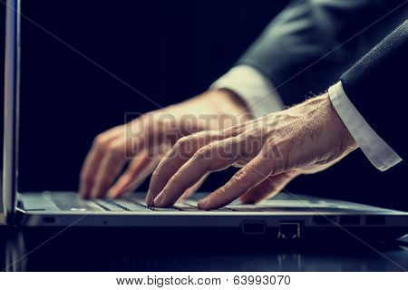 Businessman Typing On A Laptop In Darkness