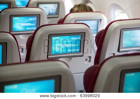 DOHA, QATAR - FEBRUARY 18, 2014: Economy class seats with entertainment system onboard. Qatar Airways Economy Class was named best in the world in the 2009 and 2010 Skytrax Awards.