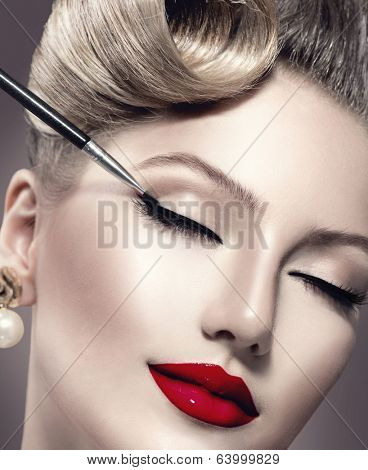 Makeup. Vintage style Make-up Applying closeup. Eyeliner. Retro styled Woman. Eyeline brush for Make up. Beauty Girl with Perfect Skin. Eyelashes. Red Lipstick. Makeover poster