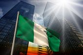 Nigeria national flag against low angle view of skyscrapers at sunset poster