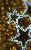 Golden Christmas background decoration. Defocused elegant abstract background with mutiple bokeh and two blue light stars poster