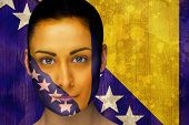 Composite image of beautiful football fan in face paint against bosnia flag in grunge effect poster
