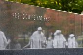 "The inscription on the wall at the Korean War Memorial in Washington DC ""Freedom Is Not Free"". The reflections of the soldier statues on the wall remind us of the cost of Freedom. Located along the National Mall. poster"