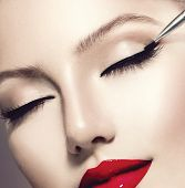 Makeup. Perfect Make-up Applying closeup. Eyeliner. Cosmetic Eyeshadows. Eyeline brush for Make up. Beauty Girl with Perfect Skin. Eyelashes. Red Lipstick. Makeover poster