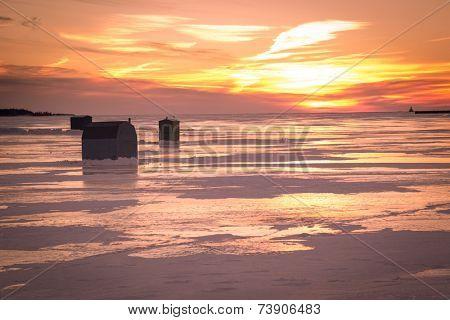 Ice fishing at sunset along the shores of rural Prince Edward Island.