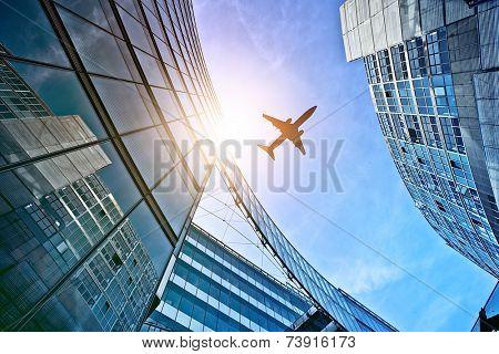 plane flying over modern glass and steel office buildings near Potsdamer Platz, Berlin, Germany