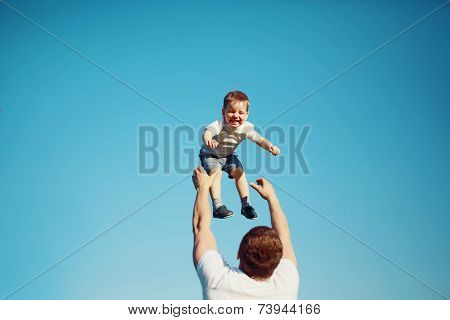 Happy Joyful Child, Father Fun Throws Up Son In The Air, Summer, Sun, Blue Sky, Family, Travel