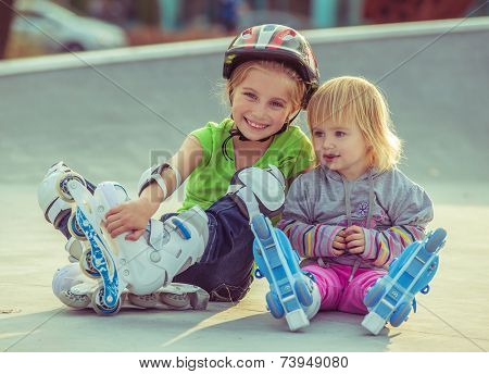 two beautiful little sisters in a roller skates sitting  on the street