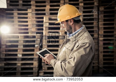 Warehouse worker doing a checklist using a PC tablet
