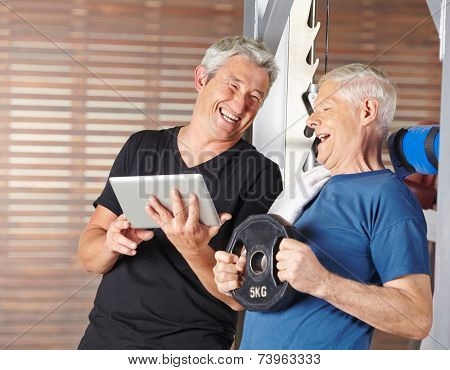 Senior men exercising in gym and laughing with tablet PC