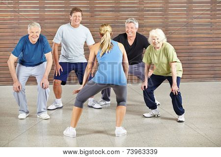 Senior people dancing to music in gym with dance instructor