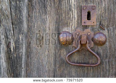 Front view of old doorknocker and wooden door