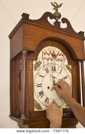 Hands Resetting Hands On Antique Clock.