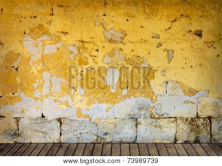 Rough wall with peeling yellow paint and wooden floor