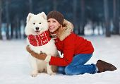 Joyful beautiful stylishly dressed young woman in red jacket hugging white Samoyed dog outdoors in the park on a winter day poster