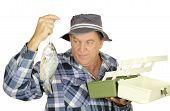 Middle aged fisherman holding freshly caught fish with open tackle box. poster