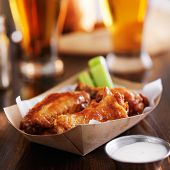 buffalo chicken wings in disposable tray with celery, ranch, and beer poster
