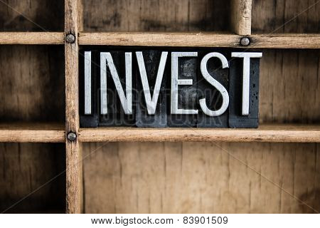 "The word ""INVEST"" written in vintage metal letterpress type in a wooden drawer with dividers. poster"