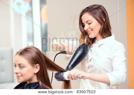 poster of Stylish by professionals you can trust.  Mirror reflection of a young beautiful hairdresser doing her clients hair with a hair drier on the background of the hairdressing salon