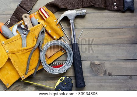 home renovation in progress. tool belt with various tools against wooden surface add your text. poster