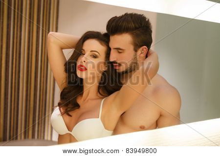 Sexy passionate couple posing at mirror young lover poster